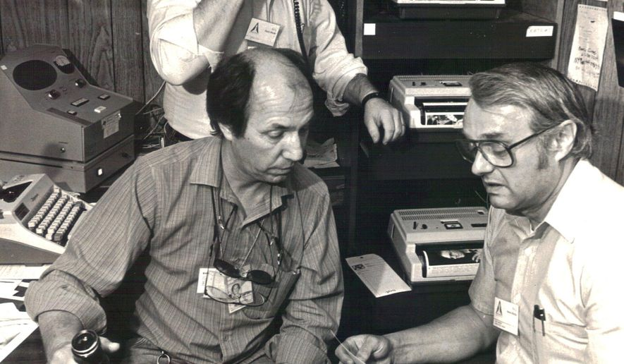 Former Washington photo editor Toby Massey, right, and Florida photo editor Phil Sandlin, left, edit photos at Kennedy Space Center during an early Space Shuttle launch as photograher Steve Pyle, rear,  coordninates transmissions with New York.   Massey, a photographer and photo editor who directed coverage of presidents and political conventions as well as natural disasters, the space program and sporting events during a 38-year career with The Associated Press, died Thursday, Aug. 21, 2014. He was 80. (AP Photo/Phil Sandlin)