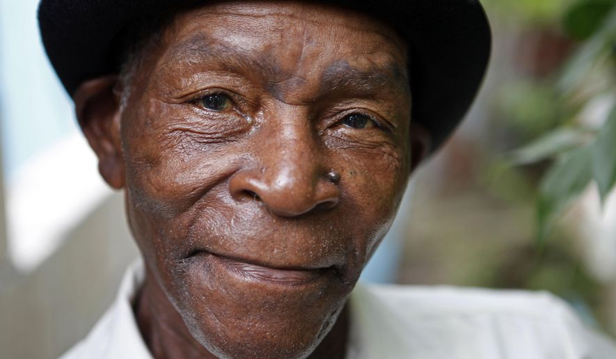"FILE - In this Aug. 13, 2011 file photo, Joseph ""Powda"" Bennett, of the band The Jolly Boys, poses for a portrait in Port Antonio, Jamaica. The Jamaican folk musician died in his Caribbean homeland at age 76 on Wednesday, Aug. 20, 2014. The Jolly Boys played a rollicking genre of Jamaican folk music known as Mento. (AP Photo/Caterina Werner, File)"