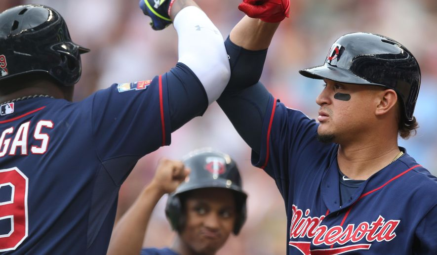 Minnesota Twins' Oswaldo Arcia, right, gives an elbow bump to Kennys Vargas as a ball boy, center, waits his turn after Vargas hit a solo home run off Cleveland Indians pitcher Corey Kluber in the fourth inning of a baseball game, Thursday, Aug. 21, 2014, in Minneapolis. (AP Photo/Jim Mone)