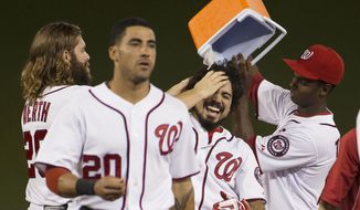 Washington Nationals' Jayson Werth, left, and Michael Taylor, right, dump water on teammate Anthony Rendon after he hit the game-winning single in a baseball game against the Arizona Diamondbacks on Wednesday, Aug. 20, 2014, in Washington. In front is Ian Desmond. The Nationals won 3-2. (AP Photo/Evan Vucci)