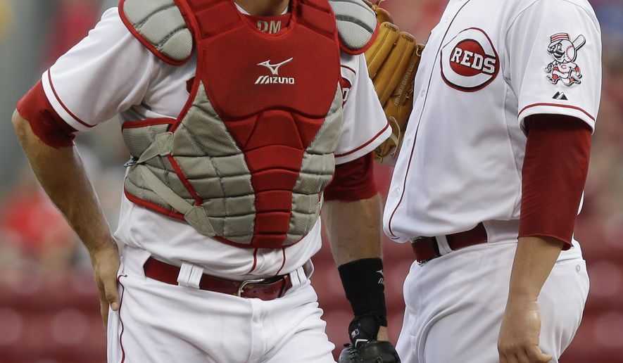 Cincinnati Reds starting pitcher David Holmberg, right, talks with catcher Devin Mesoraco in the first inning of a baseball game against the Atlanta Braves, Thursday, Aug. 21, 2014, in Cincinnati. (AP Photo/Al Behrman)