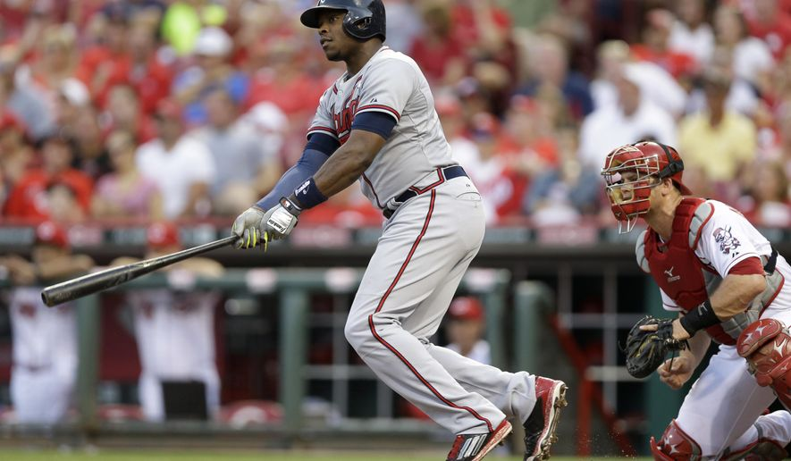 Atlanta Braves' Justin Upton watches his hit off Cincinnati Reds starting pitcher David Holmberg with the bases loaded to drive in two runs in the third inning of a baseball game, Thursday, Aug. 21, 2014, in Cincinnati. Reds catcher Devin Mesoraco is at right. (AP Photo/Al Behrman)