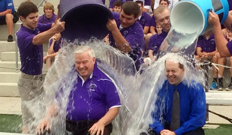 """In this Thursday, Aug. 21, 2014, photo provided by the Archdiocese of Cincinnati, Jim Rigg, right, superintendent of the diocese's 113 schools, and Elder High School Principal Tom Otten take the ice-bucket challenge at Elder High School in Cincinnati. The archdiocese is discouraging its students and staff from donating any money raised as part of the challenge to the ALS Association, saying the group funds a study involving embryonic stem cell research """"in direct conflict with Catholic teaching."""" The diocese said schools could participate in the ice bucket challenge, but any money raised should be directed to groups like the John Paul II Medical Research Institute in Iowa City, Iowa, which conducts """"pro-life driven"""" research, according to its website. (AP Photo/Archdiocese of Cincinnati)"""