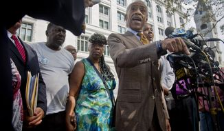 Esaw Garner, right partially obscured, the wife of fatal police chokehold victim Eric Garner, his mother Gwen Carr, center, and her husband Benjamin Carr, second from left, stand with Rev. Al Sharpton, second from right, as he speaks at a press conference after the family met privately with U.S. Attorney Loretta Lynch on Thursday Aug. 21, 2014 in New York.  The family of the unarmed Eric Garner, whose death last month in police custody was recorded on video, has asked federal prosecutors to investigate the case.(AP Photo/Bebeto Matthews)