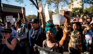 Christine Allen raises her fist while protesting with several hundred others in Oakland, Calif. on Wednesday, Aug. 20, 2014 against the shooting of Michael Brown, an unarmed black 18-year old by a white police officer in Ferguson, Mo. (AP Photo/Noah Berger)