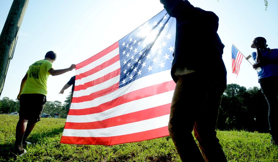 Meigs Middle School eighth-graders Andrew Steele, left, and Christian McIntosh hold an American flag on Thursday, Aug. 21, 2014 in Shalimar, Fla., to honor the arrival of Army Sgt. 1st Class Sam Hairston's body. Hairston died while fighting in Afghanistan. (AP Photo/Northwest Florida Daily News, Nick Tomecek)
