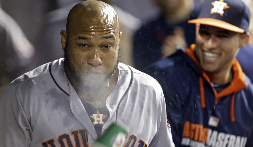 Houston Astros' Jon Singleton gets doused with water in the dugout after a three-run home run against the Cleveland Indians in the ninth inning of a baseball game Friday, Aug. 22, 2014, in Cleveland. (AP Photo/Mark Duncan)