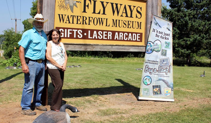 ADVANCE FOR MONDAY AUG. 25 - In this Aug. 8, 2014 photo, Craig and Nichol Swenson pose near the sign for Flyways Waterfowl Museum in Baraboo, Wis. Nichol and Craig Swenson, who opened Flyways Waterfowl Museum near the north shore entrance to Devil's Lake State Park last summer, are living out their mission of conservation. (AP Photo/Baraboo News Republic, Annie Getsinger)