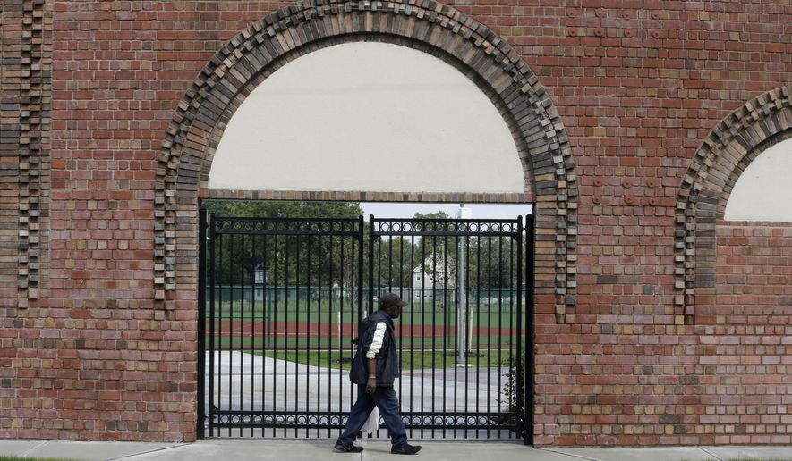 In this Thursday, Aug. 21, 2014 photo, Joe James, 83, walks past an entrance with the original wall at League Park in Cleveland. The city of Cleveland has invested $6.3 million in restoring the old site of League Park, a historic site where the Cleveland Indians clinched their 1920 World Series title, Babe Ruth hit his 500th home run and where Joe DiMaggio extended his hitting streak to 56 games. Not much of the old ballbark, where Cy Young threw the first pitch in 1891 remains, but the new park will host high school and youth games on its all-turf field and will pay homage to the greats who once played there. (AP Photo/Tony Dejak)