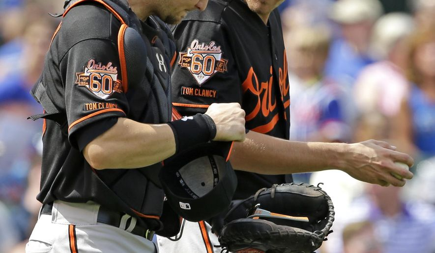 Baltimore Orioles starter Kevin Gausman, right, talks with catcher Caleb Joseph during the third inning of an interleague baseball game against the Chicago Cubs in Chicago, Friday, Aug. 22, 2014. (AP Photo/Nam Y. Huh)