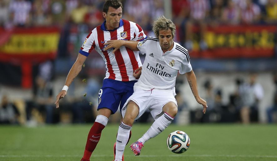 Real Madrid Fabio Coentrao from Portugal, right, duels for the ball with Atletico Madrid's Mario Mandzukic from Croatia during a Spanish Super Cup soccer match at the Vicente Calderon stadium in Madrid, Spain, Friday, Aug. 22, 2014 . (AP Photo/Daniel Ochoa de Olza)
