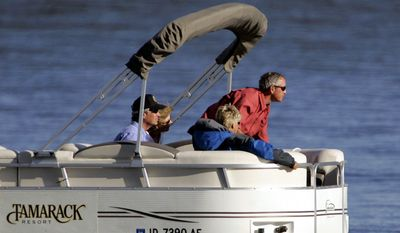 President Bush, right, leans forward as his boat approaches the dock following a tour on Lake Cascade in Donnelly, Idaho, with Idaho Gov. Dirk Kempthorne, left, and the governor's wife, Patricia Kempthorne, second right, and Laura Bush, Tuesday, Aug. 23, 2005. President Bush arrived Monday afternoon by helicopter in Donnelly, where he's due to spend two nights at the ski and golf resort that opened in December 2004. (AP Photo/Elaine Thompson)