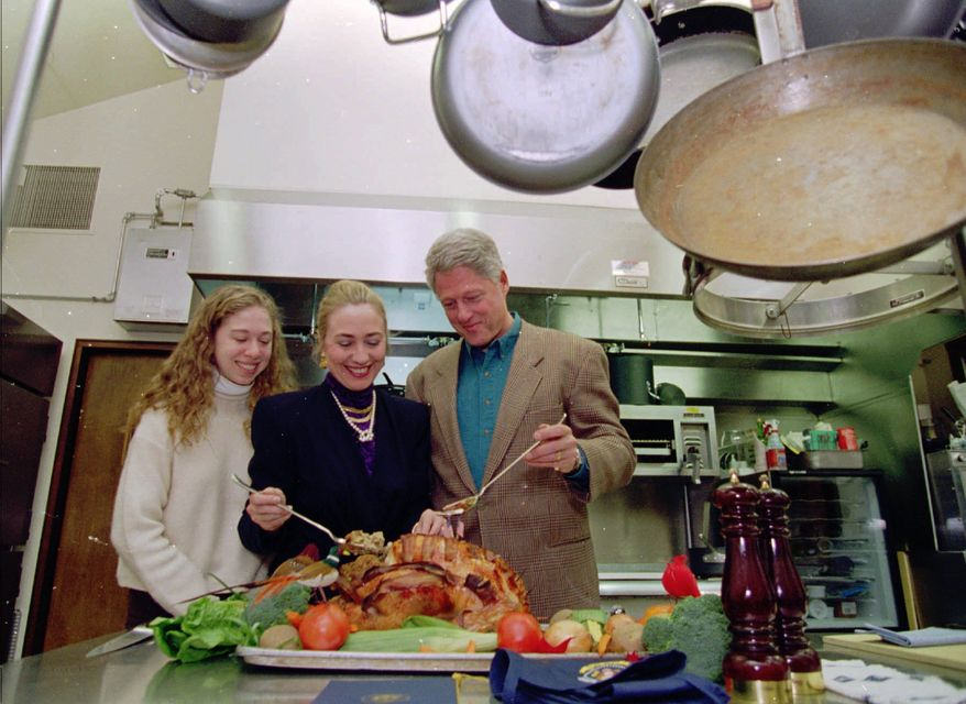 President and Mrs. Clinton and their daughter Chelsea look over their Thanksgiving Day turkey Thursday, Nov. 23, 1995 in a kitchen of the presidential retreat Camp David, Md. (AP Photo/The White House, Sharon Farmer)