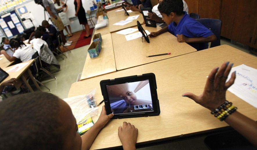 FILE - In this Aug. 27, 2013, file photo, Muhammad Nassar Jr. takes a picture of himself during Karen Finkel's class at Broadcrest Elementary School in Carson, Calif. An internal report concludes the Los Angeles Unified School District's $1 billion plan to provide iPads to all students was beset by poor planning and a flawed bidding process, the Los Angeles Times reported Friday, Aug. 22, 2014. (AP Photo/Los Angeles Times, Bob Chamberlin, File) NO FORNS; NO SALES; MAGS OUT; ORANGE COUNTY REGISTER OUT; LOS ANGELES DAILY NEWS OUT;  INLAND VALLEY DAILY BULLETIN OUT; MANDATORY CREDIT, TV OUT