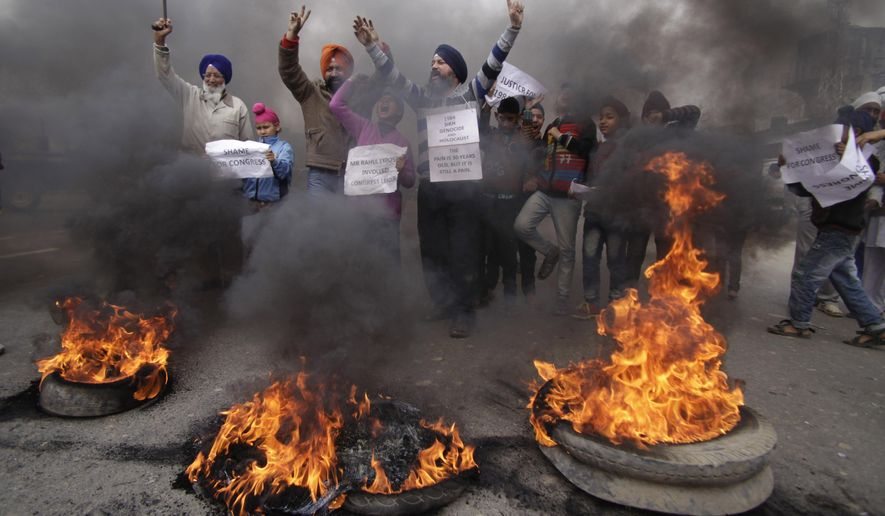FILE - In this Sunday, Feb. 2, 2014 file photo, Indian Sikh protesters shout slogans and burn tires during a protest against Congress party leader Rahul Gandhi for his recent remark on the country's 1984 anti-Sikh riots, in Jammu, India. India has blocked the release of a film on the assassination of former Indian Prime Minister Indira Gandhi, Rahul's grandmother, saying it glorifies her killers and could trigger violent protests, officials said Friday, Aug. 22, 2014. India's film certification board said the film glorified the two Sikh bodyguards who killed Gandhi to avenge her suppression of an insurgency that culminated in an army assault on the Golden Temple, Sikhism's holiest shrine. (AP Photo/Channi Anand, File)