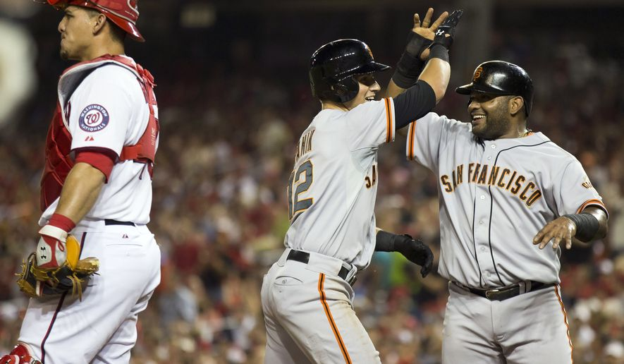 Washington Nationals catcher Wilson Ramos, left, stands at home plate as San Francisco Giants Joe Panik, center, is congratulated by Pablo Sandoval after hitting a three-run home run during the fourth inning of a baseball game on Friday, Aug. 22, 2014, in Washington. (AP Photo/Evan Vucci)