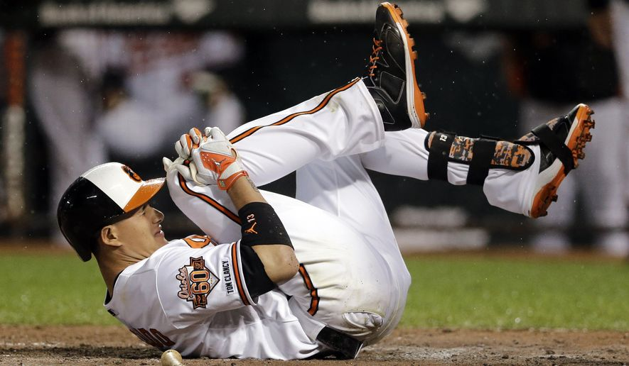 Baltimore Orioles' Manny Machado reacts after grounding out in the third inning of a baseball game against the New York Yankees, Monday, Aug. 11, 2014, in Baltimore. Machado was assisted off the field after the play. (AP Photo/Patrick Semansky)