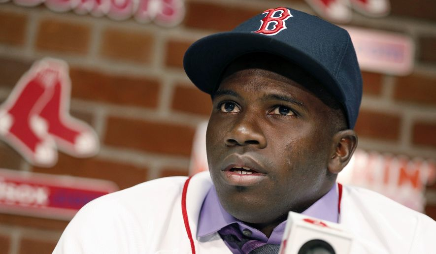 Rusney Castillo talks with reporters following a baseball game between the Boston Red Sox and the Seattle Mariners in Boston, Saturday, Aug. 23, 2014. The Red Sox announced during the game that they signed Castillo, a Cuban defector, to a seven-year contract, beginning in 2014. (AP Photo/Michael Dwyer)
