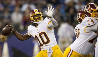 Washington Redskins' quarterback Robert Griffin III sends a pass deep during second quarter action against the Baltimore Ravens during the first quarter of their pre-season game at M&T Bank Stadium on August 23, 2014 in Baltimore, Maryland. (Pete Marovich Special to The Washington Times)
