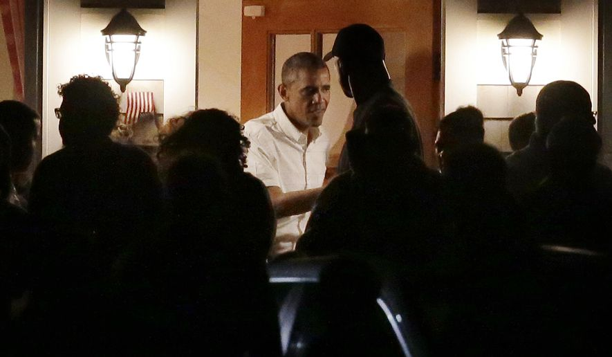 President Barack Obama, center, speaks with people on the porch while visiting with Valerie Jarrett and friends in Oak Bluffs, Mass., on the island of Martha's Vineyard, Friday, Aug. 22, 2014. Obama is vacationing for about two weeks on the island. (AP Photo/Steven Senne)