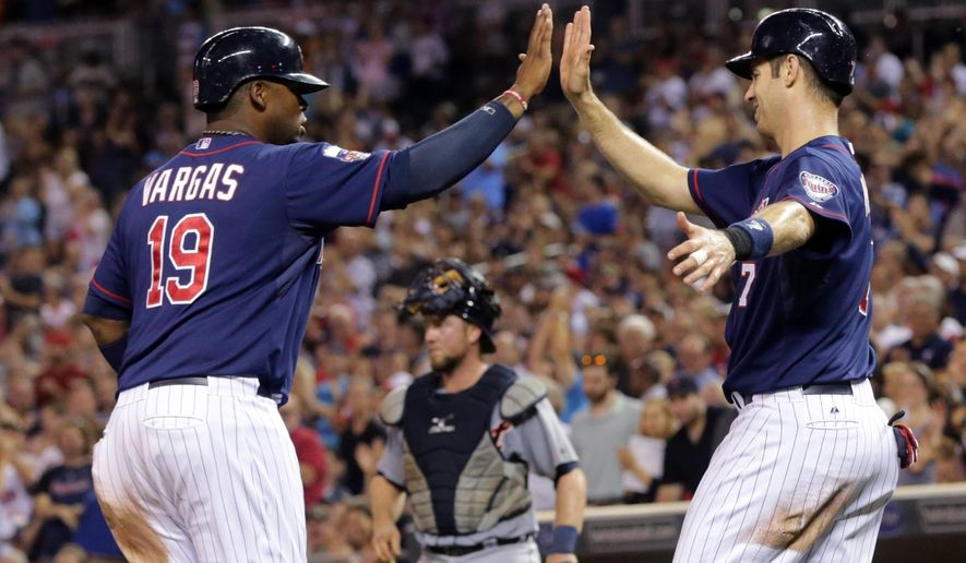 Minnesota Twins first baseman Kennys Vargas, left, and Joe Mauer, celebrate after Mauer scored on a fielder's choice and Vargas scored on a wild throw from third baseman Nick Castellanos to catcher Bryan Holaday, lower center, in the sixth inning of a baseball game, Friday, Aug. 22, 2014, in Minneapolis. (AP Photo/Jim Mone)