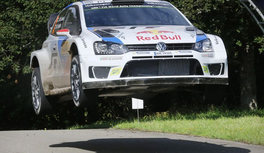 Finland's Jari-Matti Latvala and his co-pilot Mikka Anttila jump with their Volkswagen Polo during a special stage of the Deutschland Rallye in Baumholder, Germany, Saturday, Aug. 23, 2014. (AP Photo/Michael Probst)