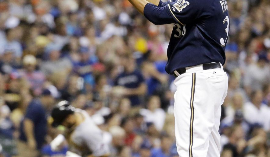 Milwaukee Brewers starting pitcher Wily Peralta reacts as Pittsburgh Pirates' Russell Martin rounds the bases after Martin hit a three-run home run during the fifth inning of a baseball game Saturday, Aug. 23, 2014, in Milwaukee. (AP Photo/Morry Gash)