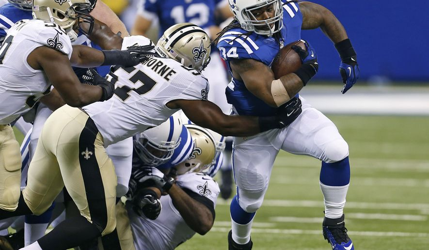 Indianapolis Colts running back Trent Richardson, right, breaks the tackle of New Orleans Saints inside linebacker David Hawthorne during the first half of an NFL preseason football game in Indianapolis, Saturday, Aug. 23, 2014. (AP Photo/Sam Riche)