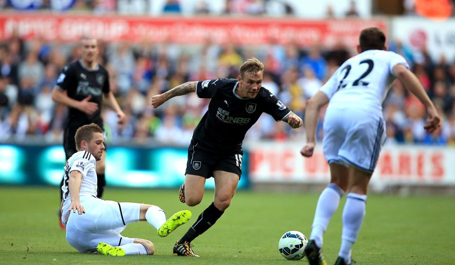 Swansea City's Gylfi Sigurdsson, left, slides in on Burnley's Matthew Taylor during the English Premier League match at the Liberty Stadium, Swansea, Wales, Saturday Aug. 23, 2014. (AP Photo/PA, Nick Potts)  UNITED KINGDOM OUT  NO SALES  NO ARCHIVE