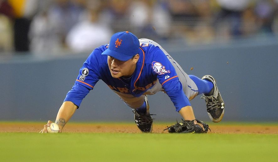 New York Mets shortstop Wilmer Flores trips while trying to throw out Los Angeles Dodgers' Yasiel Puig at first base during the fifth inning of a baseball game, Friday, Aug. 22, 2014, in Los Angeles. Puig was safe at first on the play. (AP Photo/Mark J. Terrill)
