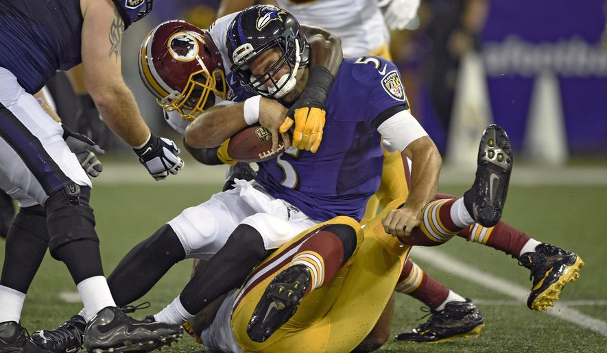 Baltimore Ravens quarterback Joe Flacco is sacked by Washington Redskins outside linebacker Brian Orakpo, top left, and defensive end Jason Hatcher in the first half of an NFL preseason football game, Saturday, Aug. 23, 2014, in Baltimore. (AP Photo/Nick Wass)