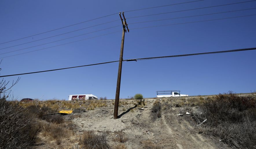 Debris and a newly-installed utility pole sit at the site of a fatal crash Friday, Aug. 22, 2014, in Oceanside, Calif. Three Japanese college students were killed and five other foreign students were injured  late Thursday, when a car carrying them veered off a California freeway and struck a utility pole, officials said Friday. (AP Photo/Gregory Bull)