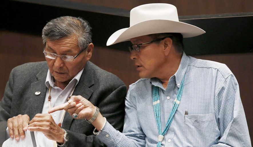 In this Friday, Aug. 1, 2014 photo, Navajo Nation President Ben Shelly, left, talks with presidential candidate Kenneth Maryboy, as they wait to speak at the Navajo Nation presidential candidate debate sponsored by the Native American Business Organization in Tempe, Ariz. There are 17 candidates in the Tuesday, Aug. 26, 2014 primary election for Navajo Nation president, where voters will determine which candidates continue to the Nov. 4, 2014 general election. (AP Photo/Ross D. Franklin)