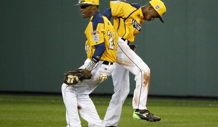 Chicago's Trey Hondras, left, celebrates with Pierce Jones (23) after Jones caught the final out of a 6-5 win over Philadelphia in an elimination baseball game at the Little League World Series tournament in South Williamsport, Pa., Thursday, Aug. 21, 2014. (AP Photo/Gene J. Puskar)