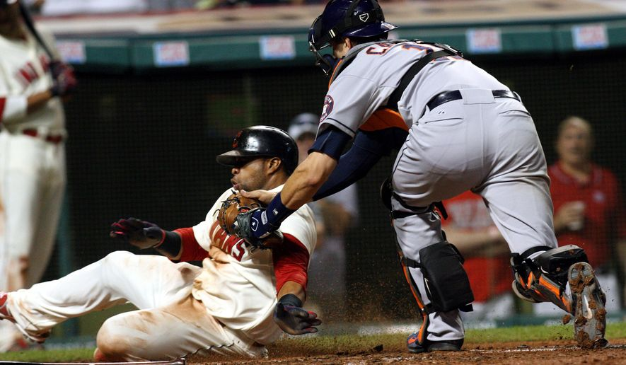 Cleveland Indians' Carlos Santana is tagged out at home plate by Houston Astros catcher Jason Castro in the eighth inning of a baseball game Saturday, Aug. 23, 2014, in Cleveland. (AP Photo/Aaron Josefczyk)