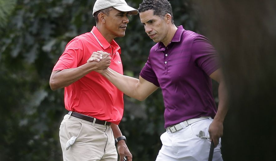 President Barack Obama, left, shakes hands with Cyrus Walker, cousin of White House senior adviser Valerie Jarrett, while golfing at Farm Neck Golf Club in Oak Bluffs, Mass., on the island of Martha's Vineyard, Saturday, Aug. 23, 2014. Obama is vacationing on the island. (AP Photo/Steven Senne)