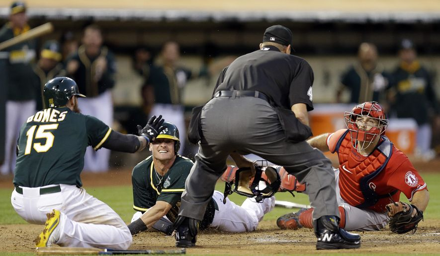 Los Angeles Angels catcher Chris Iannetta, right, and Oakland Athletics' Josh Donaldson, second from left, look to home plate umpire Chad Fairchild for the call at home plate in the sixth inning of a baseball game Saturday, Aug. 23, 2014, in Oakland, Calif. After review, Donaldson was ruled out on the play. At left is A's Jonny Gomes (15). (AP Photo/Ben Margot)