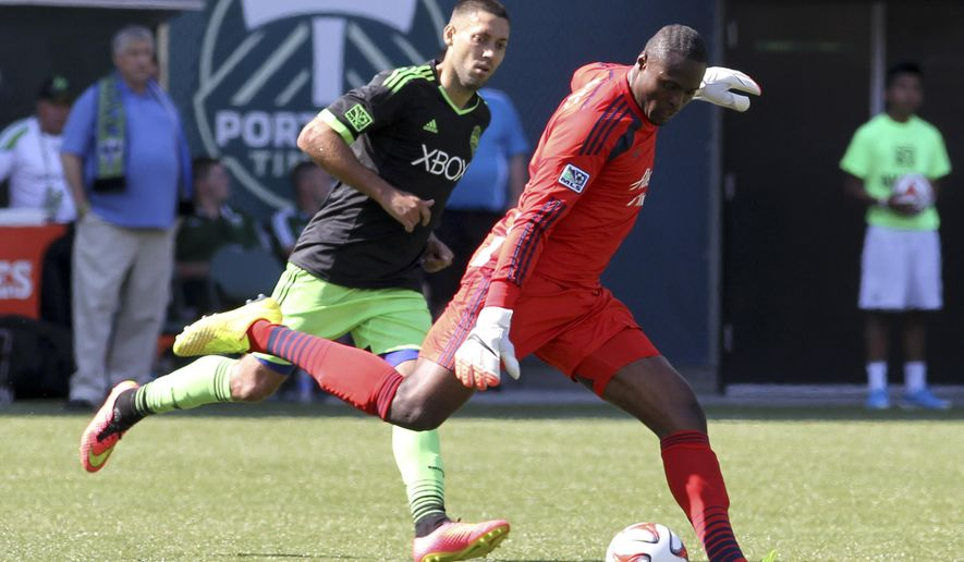 Seattle Sounders player Clint Dempsay, left, vies for the ball against Portland Timbers goalie Donovan Ricketts during an MLS soccer game in Portland, Ore., Sunday, Aug. 24, 2014. (AP Photo/Natalie Behring)