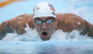 Michael Phelps of the U.S.  swims butterfly during his men's 200m individual medley at the Pan Pacific swimming championships in Gold Coast, Australia, Sunday, Aug. 24, 2014. (AP Photo/Rick Rycroft) ** FILE **
