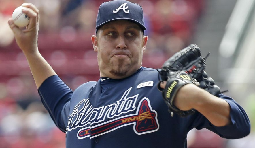 Atlanta Braves starting pitcher Aaron Harang throws against the Cincinnati Reds in the first inning of a baseball game, Sunday, Aug. 24, 2014, in Cincinnati. (AP Photo/Al Behrman)