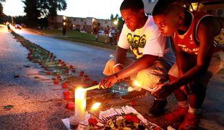 Mourners light candles at a memorial on Canfield Drive in Ferguson, Missouri, where unarmed Michael Brown was fatally shot by a police officer.