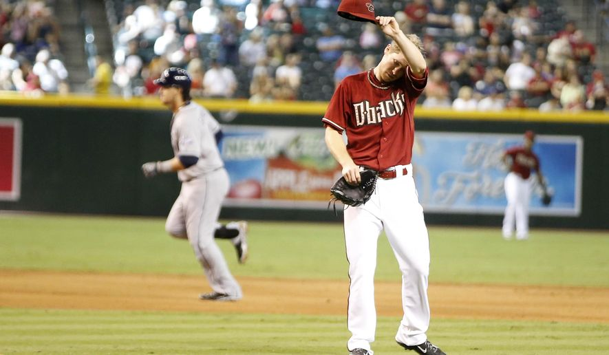 San Diego Padres' Yasmani Grandal rounds the bases as Arizona Diamondbacks' pitcher Chase Anderson wipes his brow after giving up the three run home run to Grandal in the fifth inning during a baseball game, Sunday, Aug. 24, 2014, in Phoenix. (AP Photo/Darryl Webb)