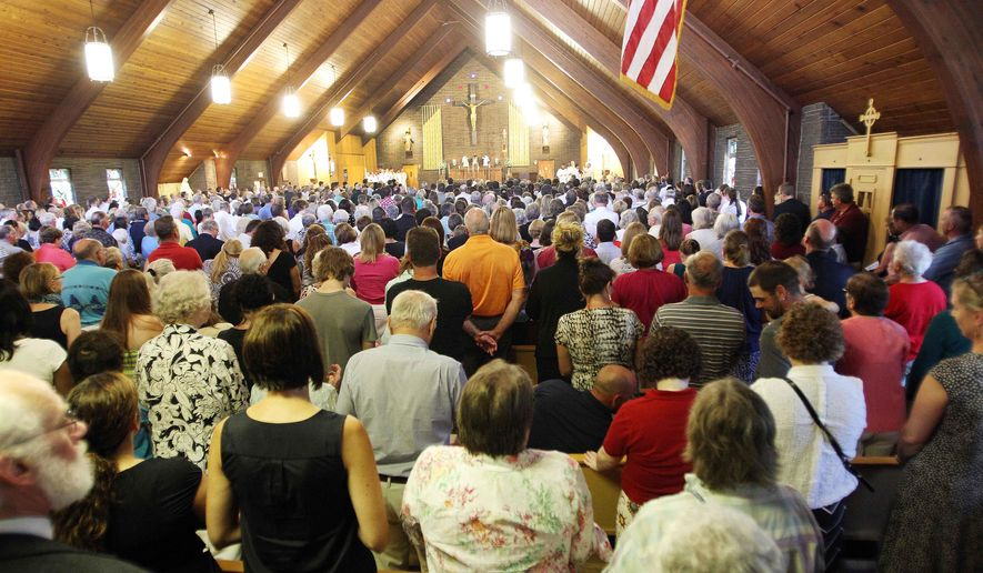 Mourners pack Our Lady of the Holy Rosary Catholic church during a special Mass for slain journalist James Foley in his hometown of Rochester, N.H., Sunday, Aug. 24, 2014. Foley was kidnapped on Thanksgiving Day 2012 while covering the Syrian uprising. The Islamic State group posted a Web video on Tuesday, Aug. 19, showing his killing and said it was in retaliation for U.S. airstrikes in northern Iraq. (AP Photo/Jim Cole)