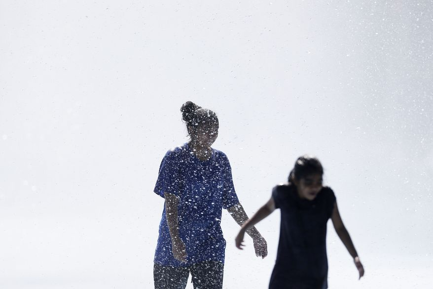 Young women play in the fountains surrounding the Unisphere at Flushing Meadows Corona Park in New York Sunday, Aug. 24, 2014. (AP Photo/Matt Rourke)