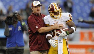Washington Redskins head coach Jay Gruden, left, greets defensive back Akeem Davis before an NFL preseason football game against the Baltimore Ravens, Saturday, Aug. 23, 2014, in Baltimore. (AP Photo/Gail Burton)
