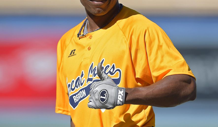 New York Mets' Curtis Granderson gives a thumbs-up as he wears a jersey from Great Lakes Region-champion Jackie Robinson West All Stars Little League team prior to the Mets' baseball game against the Los Angeles Dodgers, Saturday, Aug. 23, 2014, in Los Angeles. The Jackie Robinson team advanced Saturday to meet South Korea in Sunday's championship game of the Little League World Series. (AP Photo/Mark J. Terrill)