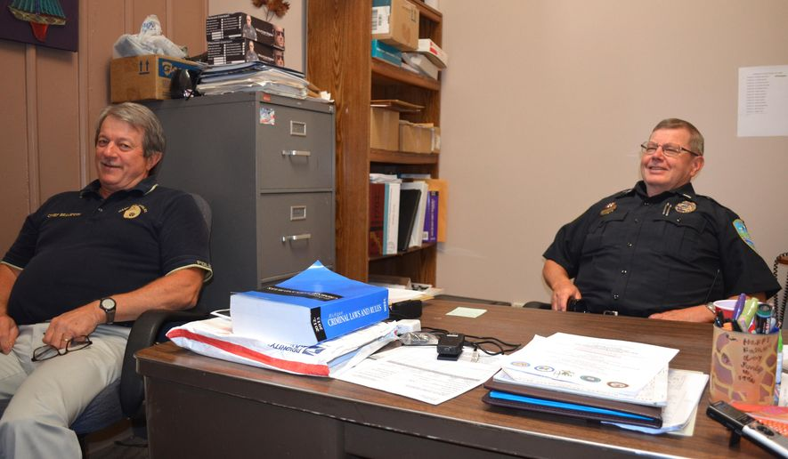 In a Aug. 14, 2014 photo, Mike Beaudoin, Hancock Chief of Police, left, and Lt. Randy Mayra, talk to a visitor in Hancock, Mich. Beaudoin and Mayra have been on the Hancock Police Department together for almost 40 years, and both will retire two days apart in October. (AP Photo/Daily Mining Gazette, Kurt Hauglie)