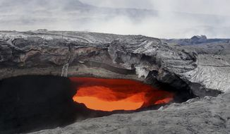 This Aug. 12, 2014 photo released by the U.S. Geological Survey shows a fluid lava stream within the main tube of the June 27 lava flow from the Kilauea volcano Pahoa, Hawaii. The June 27 lava flow, named for the date it began erupting from a new vent, isn't an immediate threat to homes or structures downhill of the flow, but could become one in weeks or months if it continues to advance, the U.S. Geographical Survey's Hawaiian Volcano Observatory said. (AP Photo/U.S. Geological Survey)