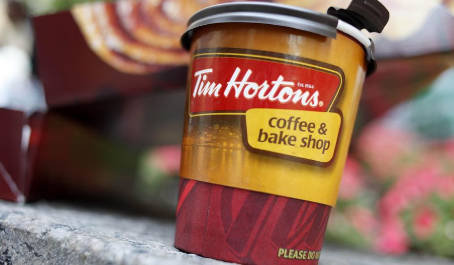 Tim Hortons locations owned by the children of its co-founders are cutting benefits after a minimum wage hike in Ontario. (AP Photo/Seth Wenig) ** FILE **