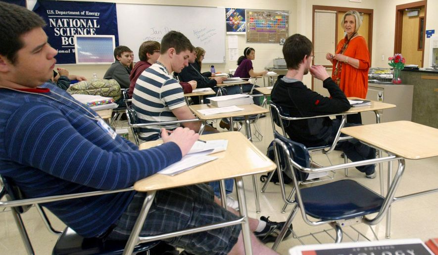 Jan Palmer, a biology teacher at Central High School in Aberdeen, S.D., top right, leads her Advanced Placement/Rising Scholars biology class through a practice test in this March 14, 2012, file photo. (AP Photo/Aberdeen American News, Kevin Bennett, File)